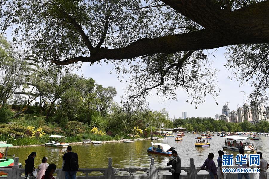 """5月31日,游客在西宁市人民公园内游玩。 """"六一""""国际儿童节来临之际,在青海省西宁市,游客在公园、海洋馆里游玩,放松心情,欢度假日。 新华社记者 张宏祥 摄"""